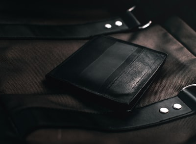 black leather bifold wallet on brown textile