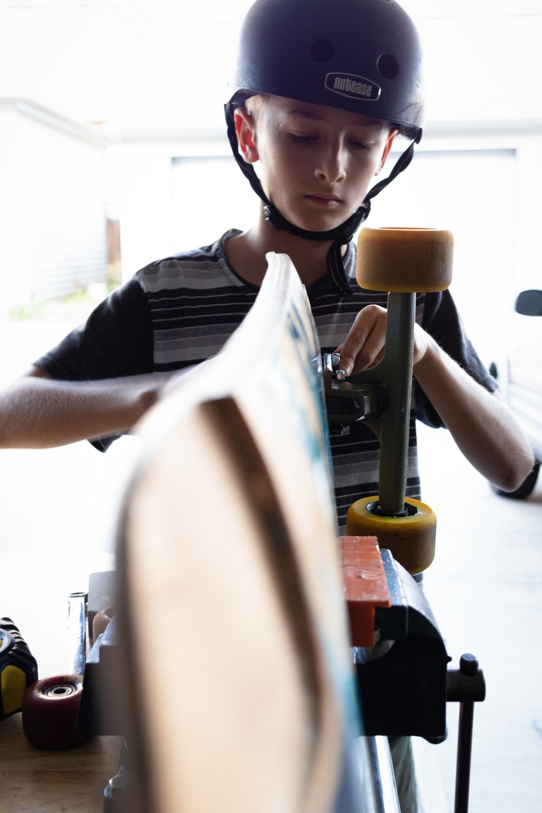 boy fixing skateboard with tools