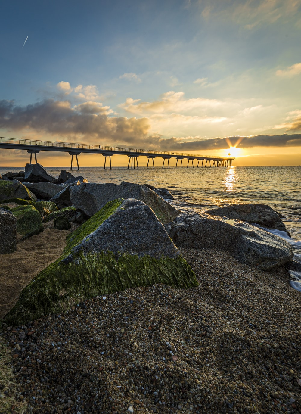 brown wooden bridge over the sea under white clouds