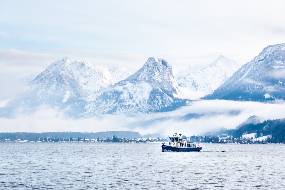 white and black boat on body of water near snow covered mountain during daytime