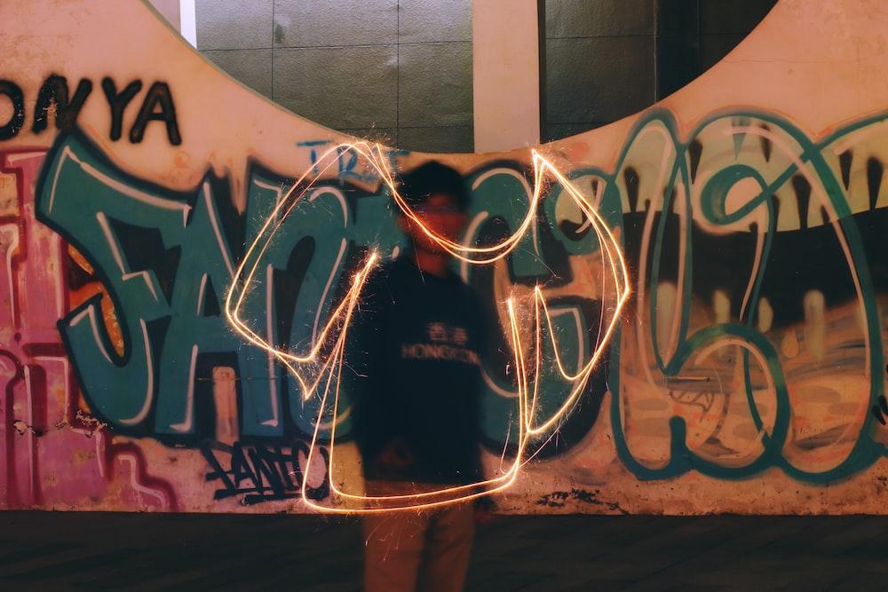 woman in black shirt standing near graffiti wall