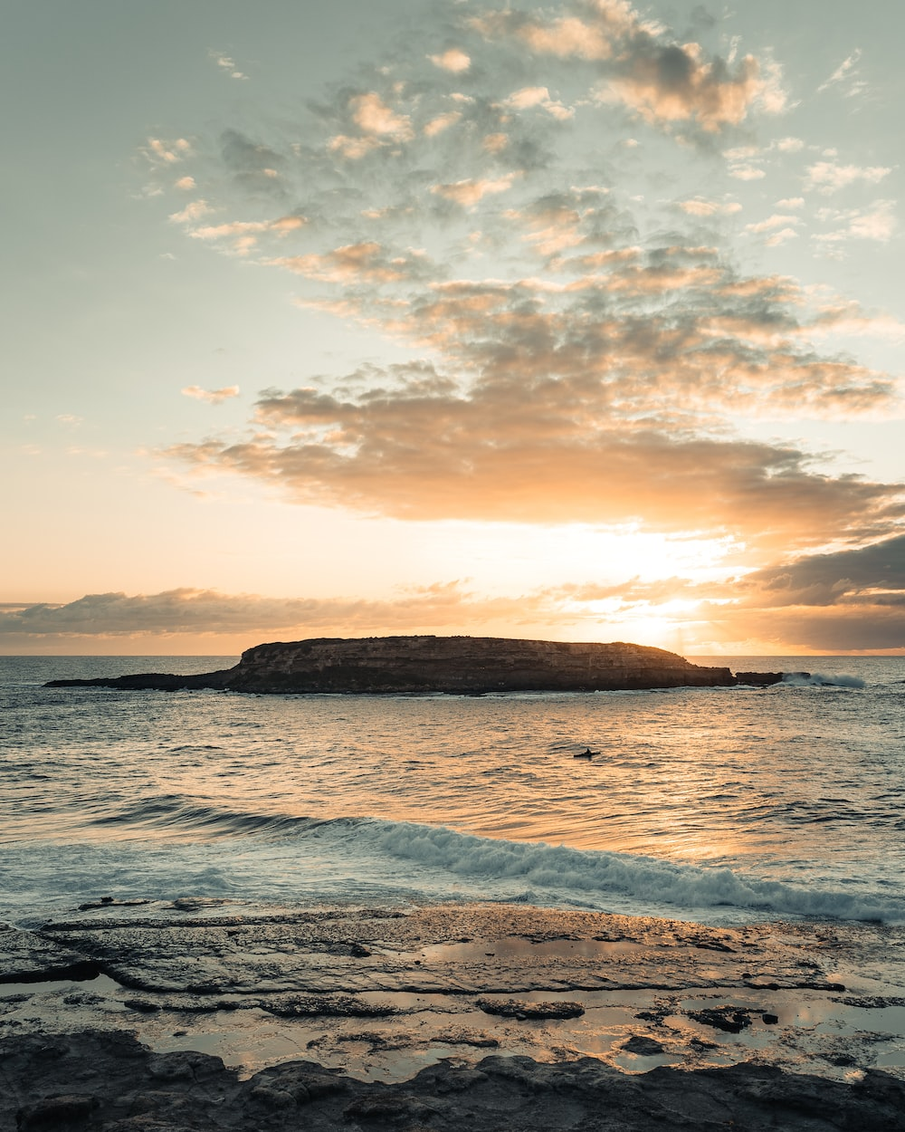 brown rock formation on sea during sunset