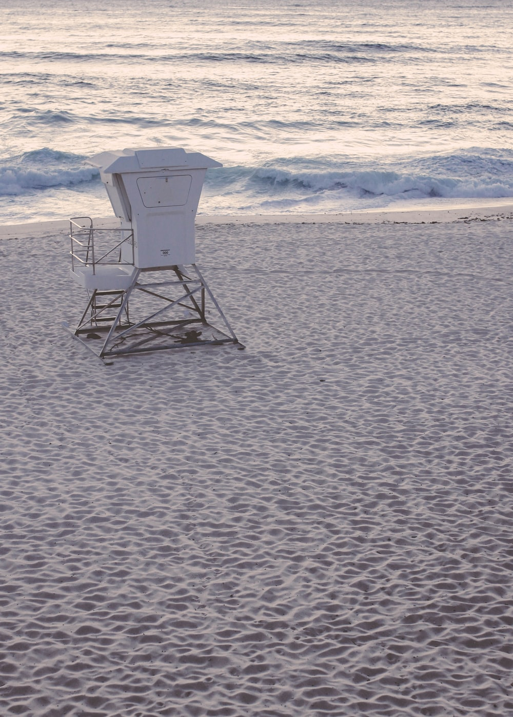 white and gray lifeguard chair on beach shore during daytime