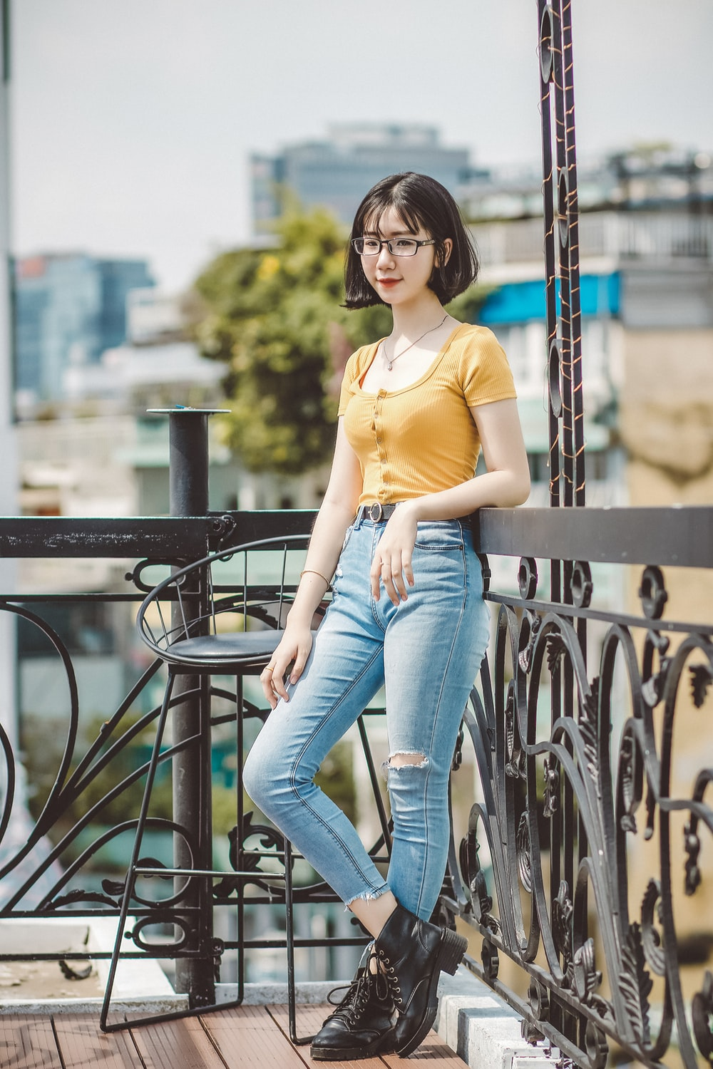 woman in yellow shirt and blue denim jeans sitting on black metal railings
