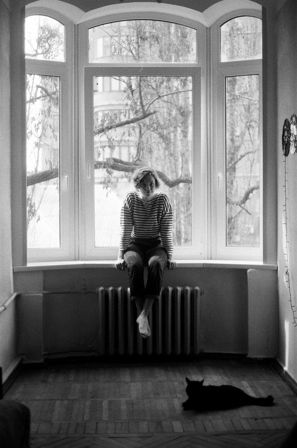 woman in striped dress sitting on window