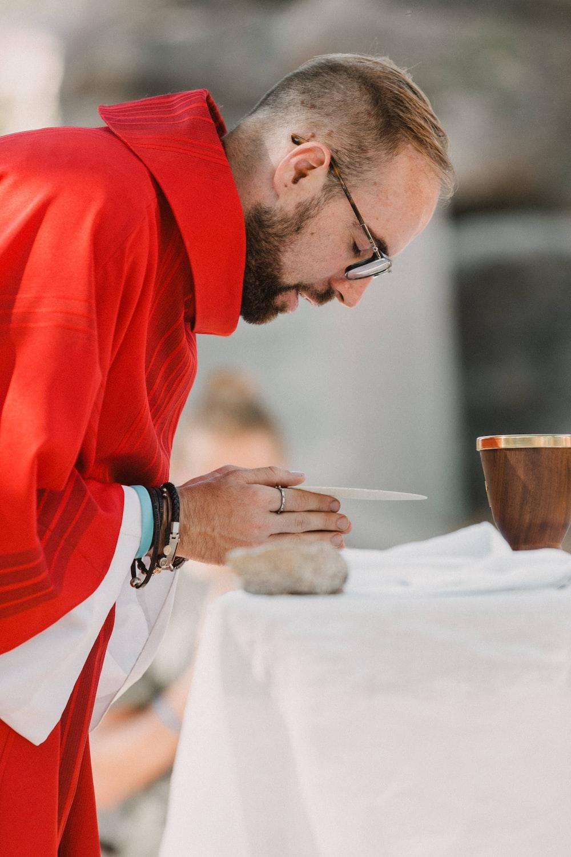 man in red long sleeve shirt holding brown ceramic mug