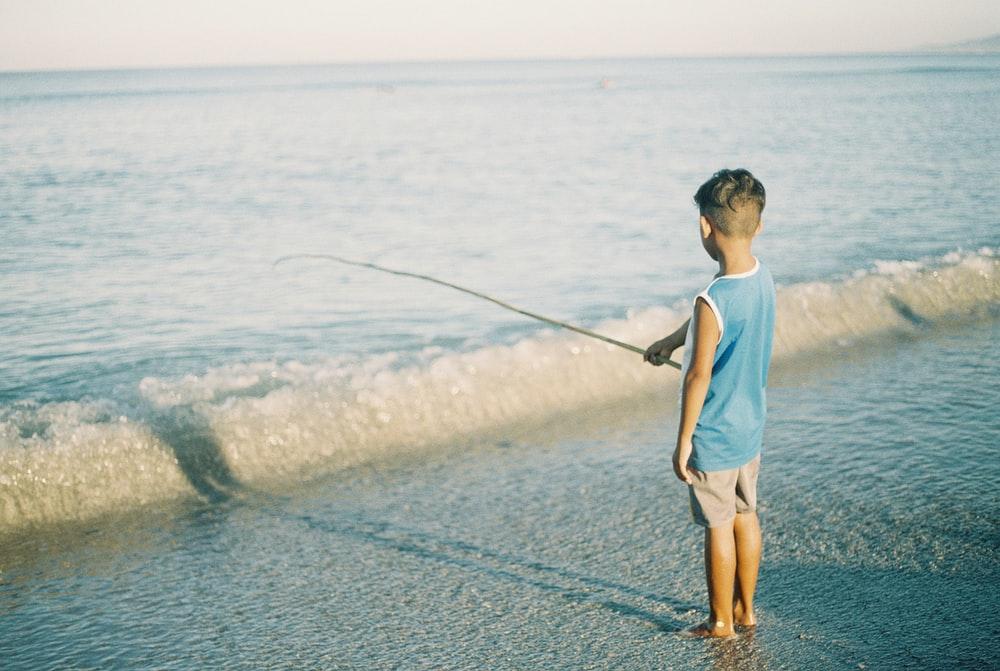 man in white crew neck t-shirt and brown shorts fishing on sea during daytime