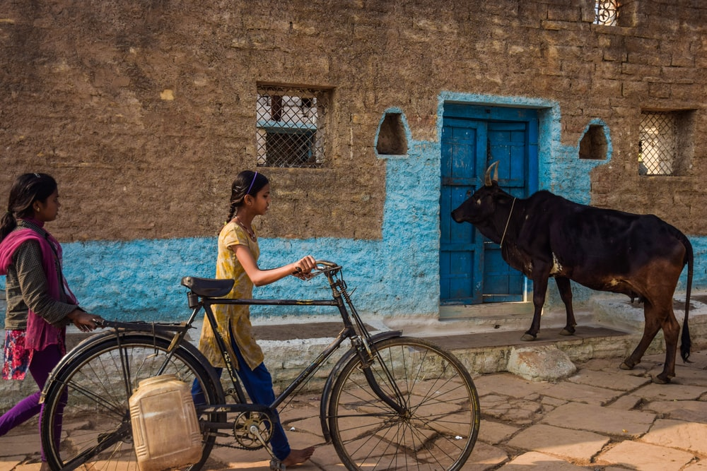 woman in brown shirt riding on black bicycle beside blue concrete building during daytime