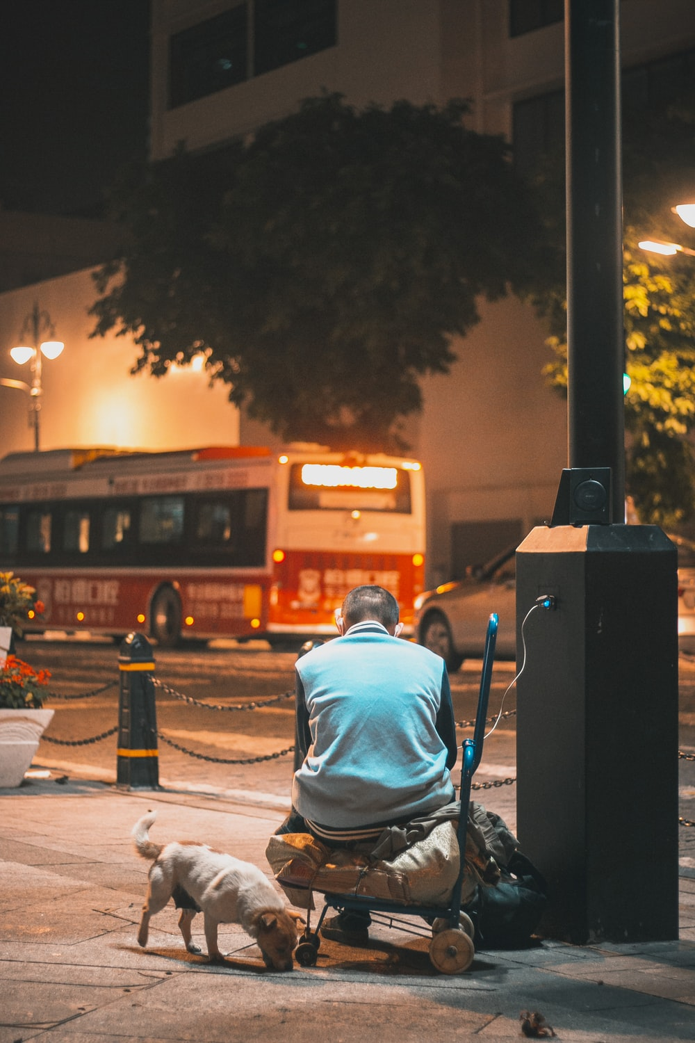 man in blue hoodie sitting on chair near road during night time