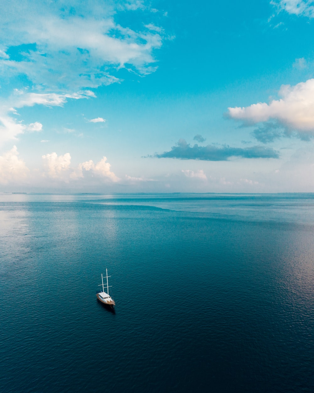 white boat on blue sea under blue sky and white clouds during daytime