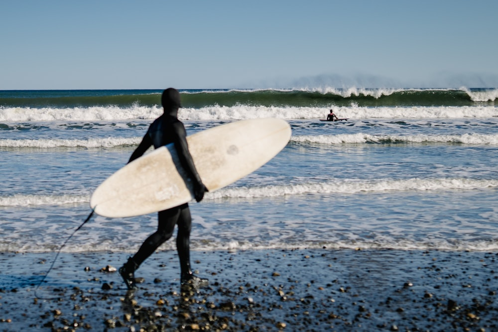 woman in black wet suit holding white surfboard walking on beach during daytime