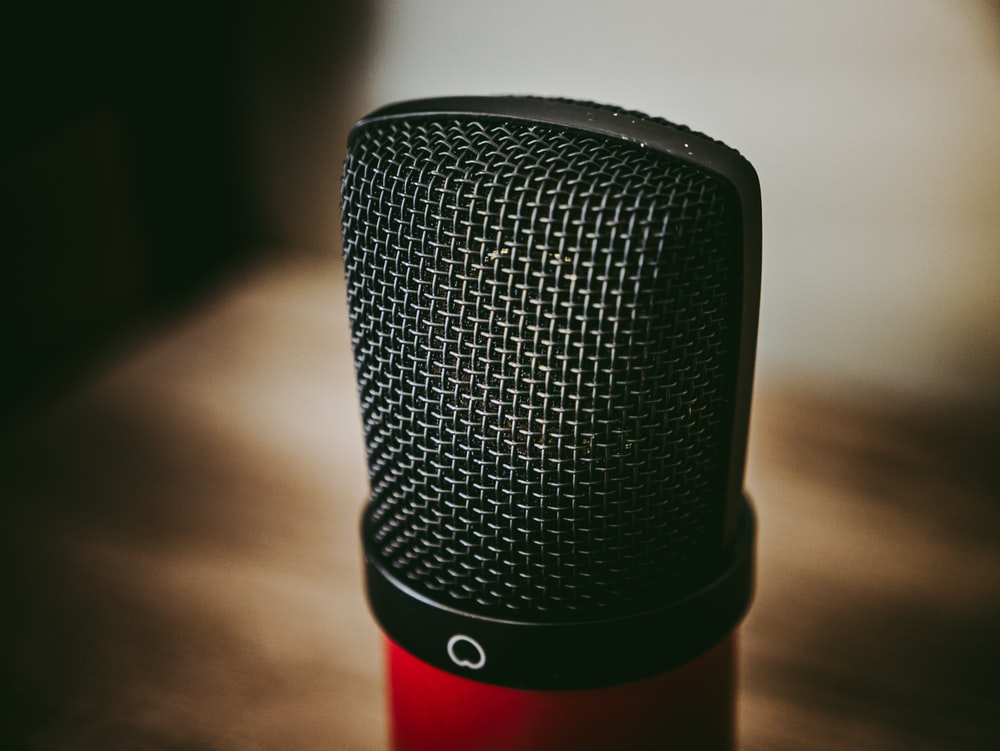 black and red microphone on brown wooden table