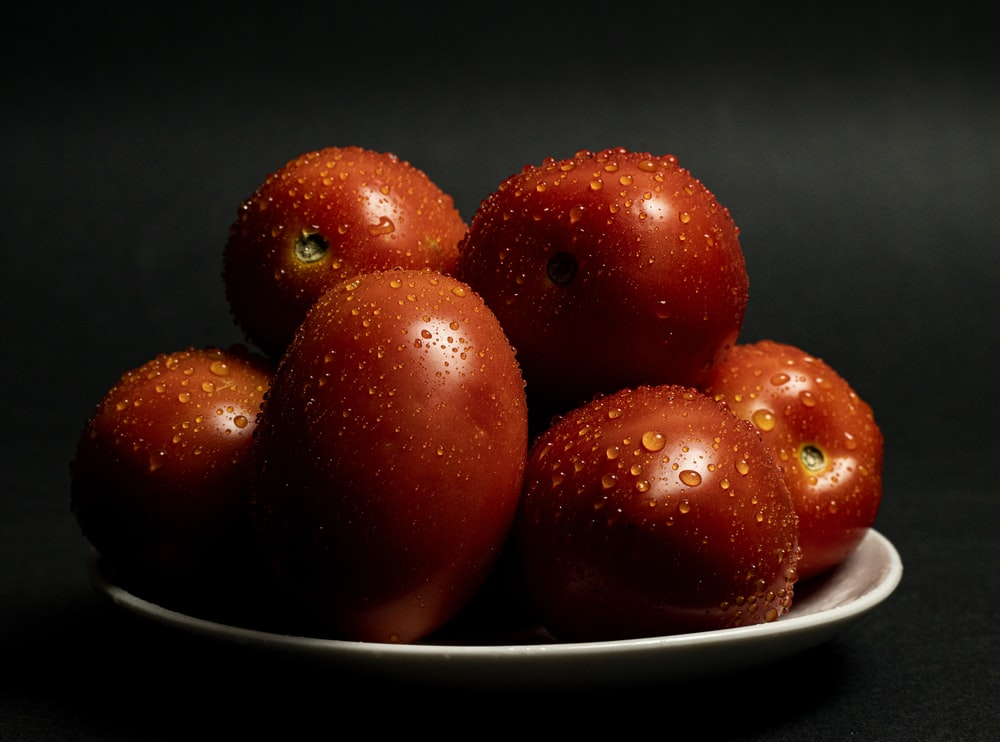 red round fruits on white ceramic bowl