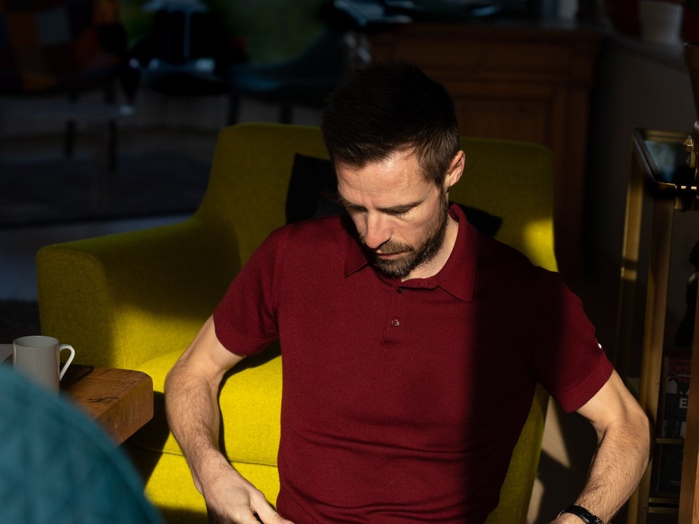 man in red polo shirt sitting on yellow chair