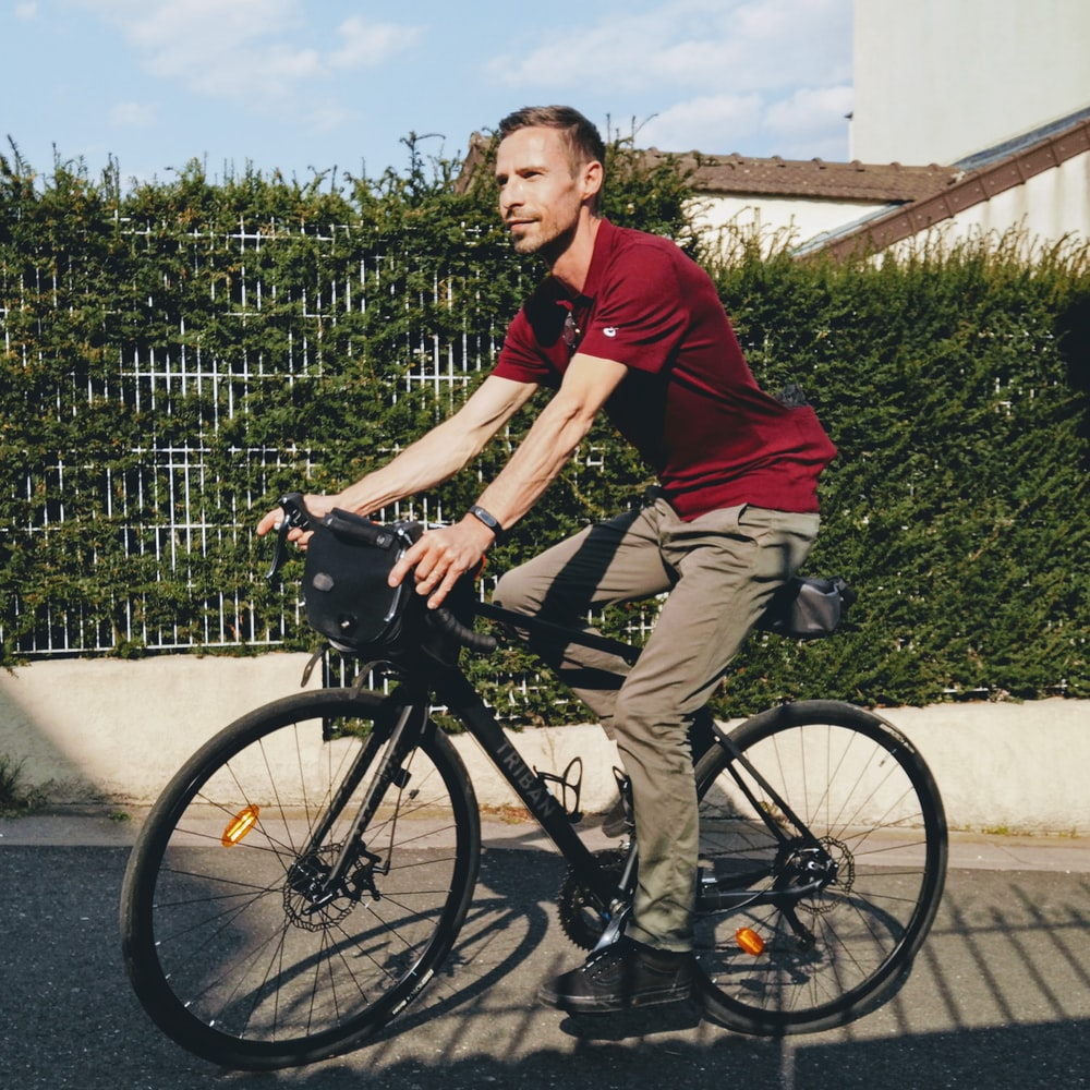man in red polo shirt riding on black bicycle