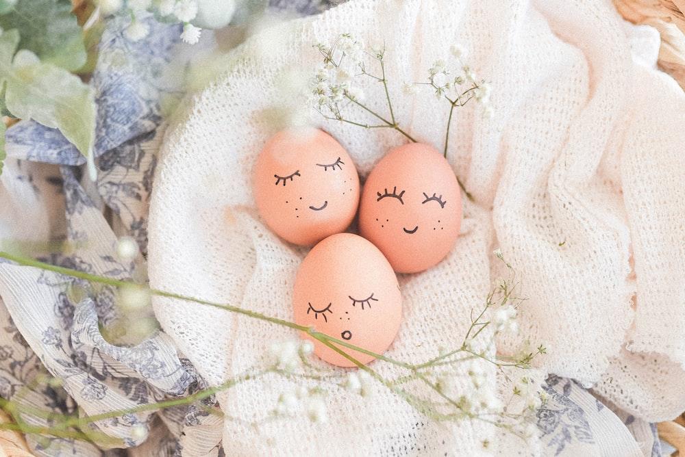 3 brown eggs on white textile