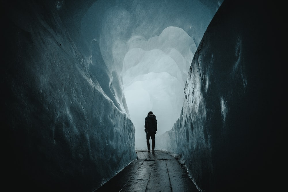 person walking on a pathway in a tunnel