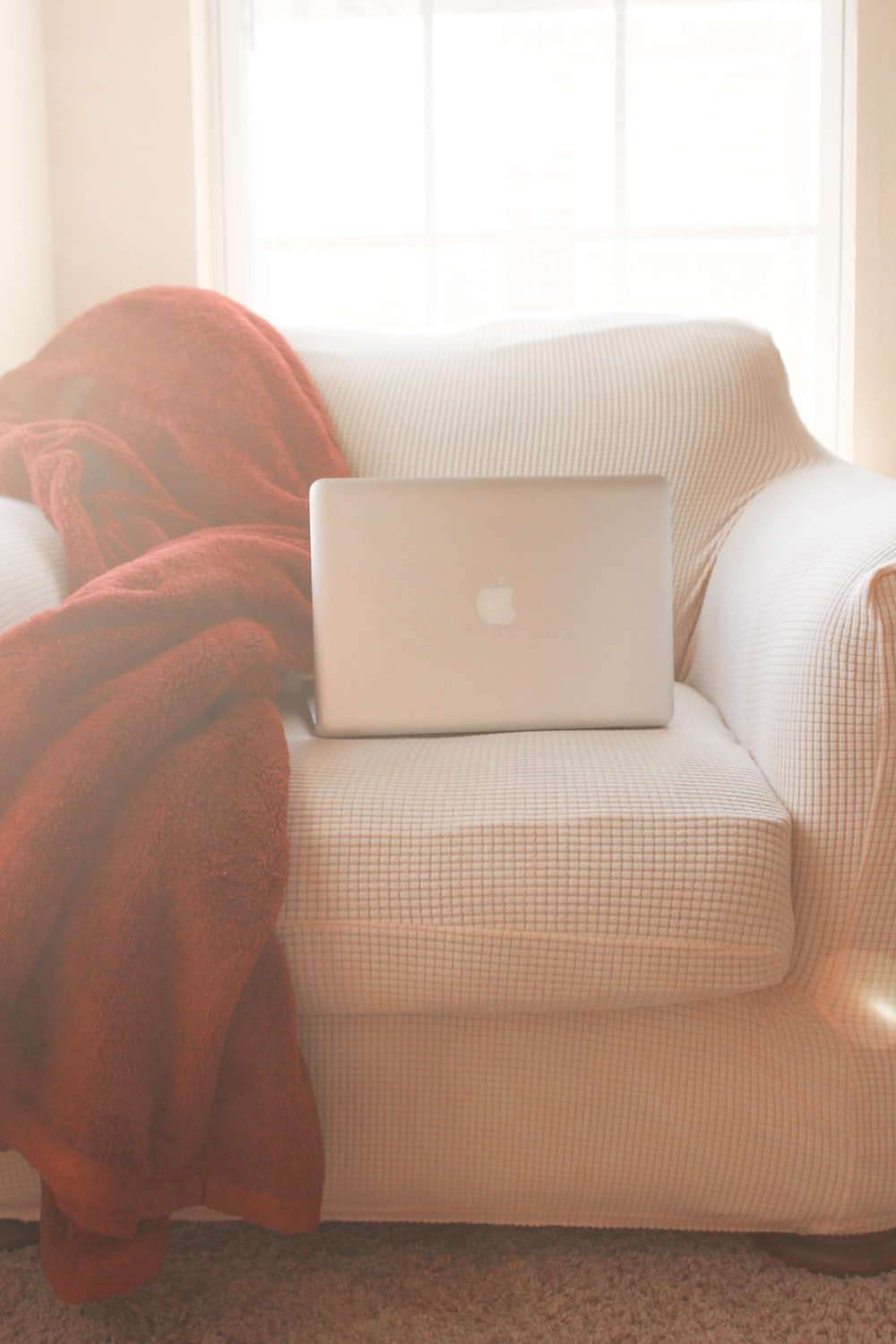silver macbook on brown textile