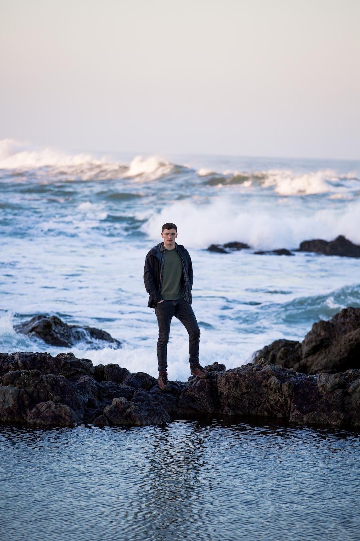 man in black jacket standing on rock near sea during daytime