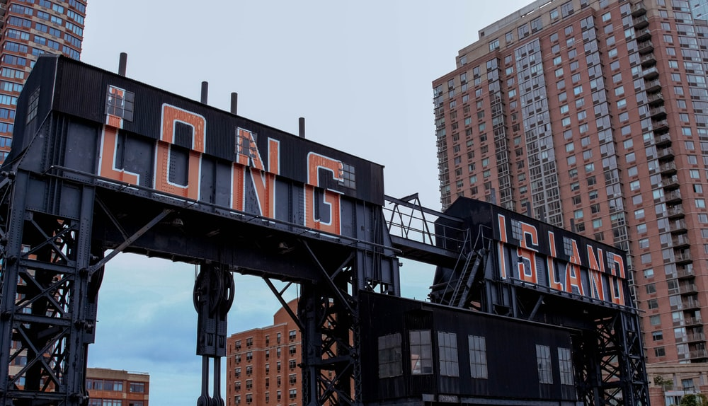 black and red metal crane near high rise buildings during daytime