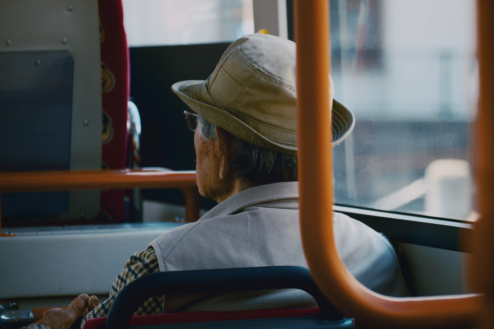 man in brown hat and gray jacket sitting on train seat