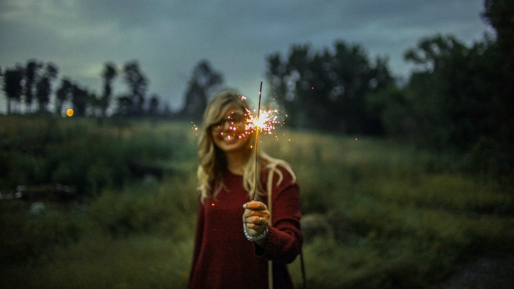 woman in red sweater holding sparkler