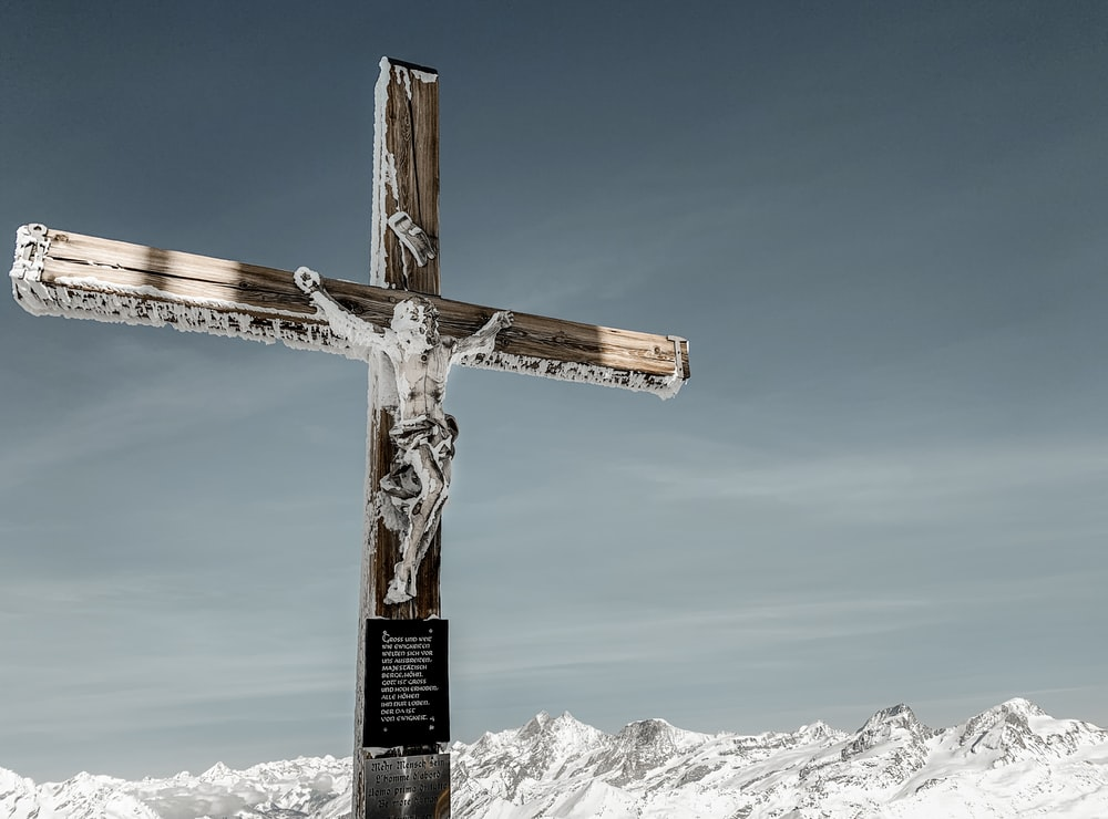brown wooden cross on snow covered mountain under blue sky during daytime
