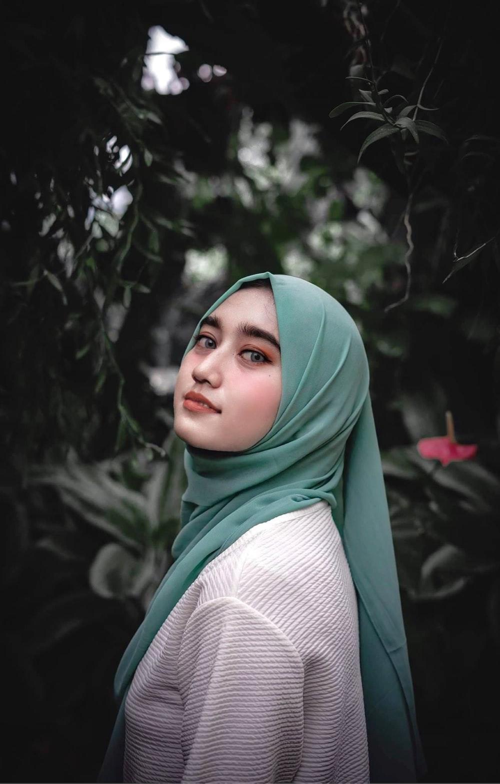woman in green hijab standing near green plants