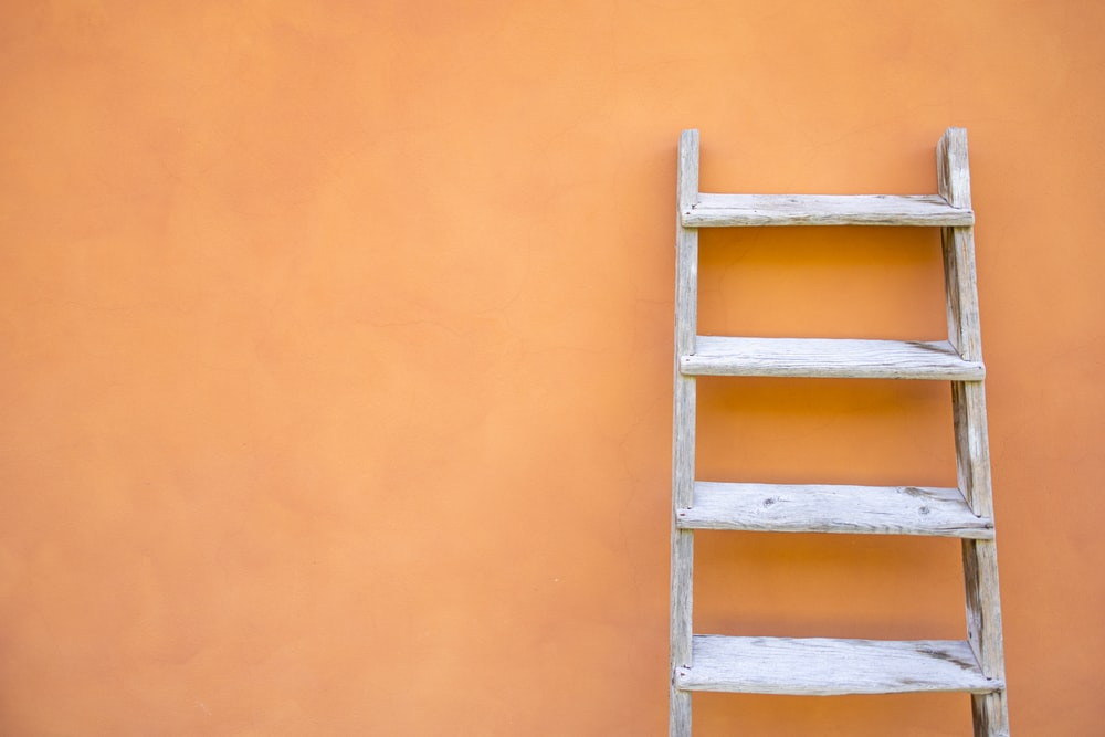 white wooden ladder leaning on orange wall