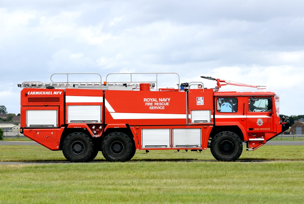 red and white fire truck on green grass field during daytime