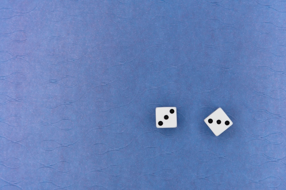 white and black dice on blue textile