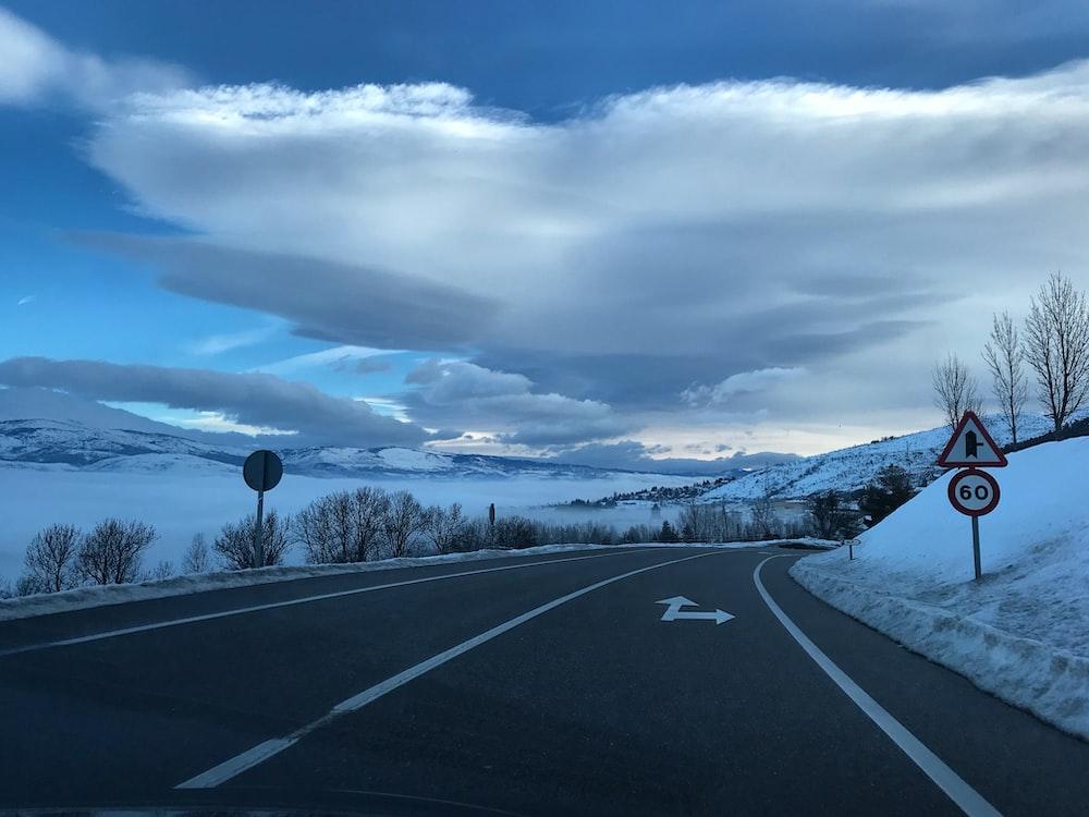 gray asphalt road under cloudy sky during daytime