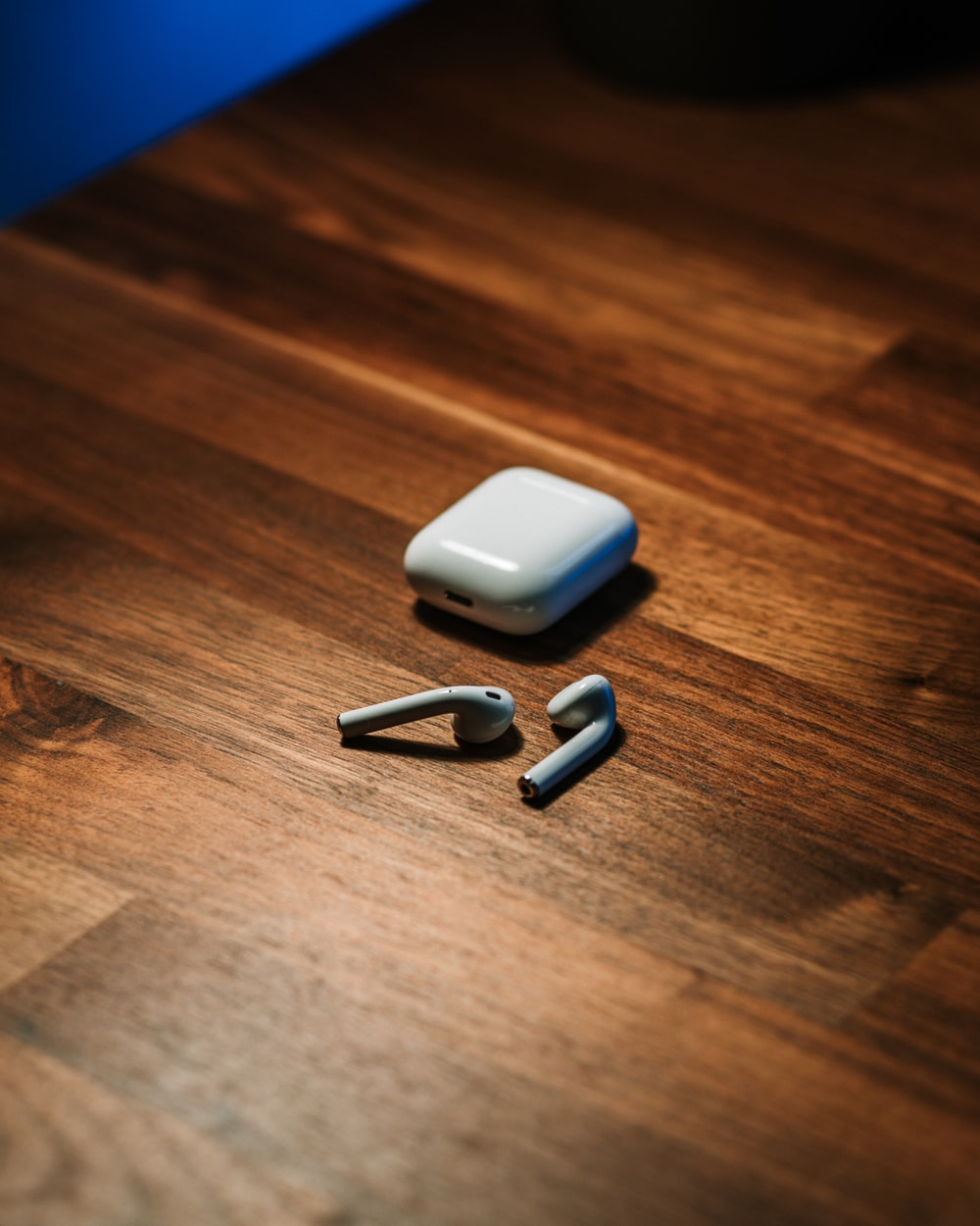 white apple airpods on brown wooden table