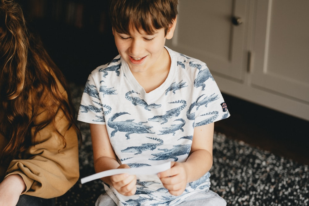 boy in white and blue floral button up t-shirt sitting on black and white textile