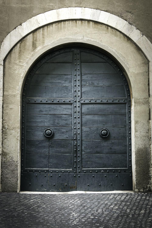 blue wooden door on brown concrete wall