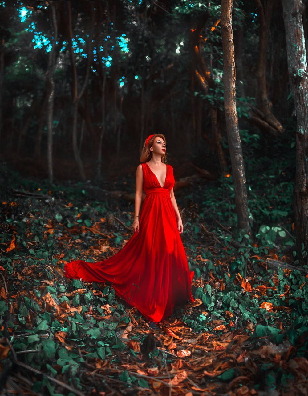 woman in red dress standing on dried leaves