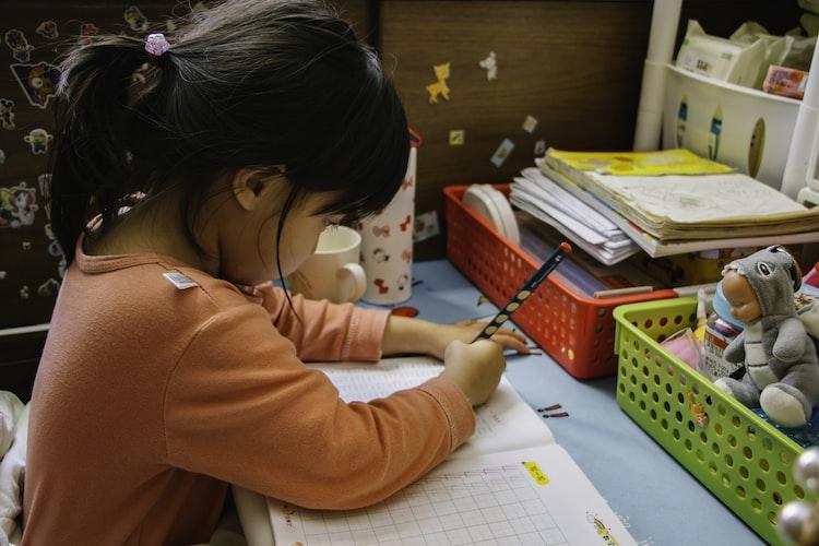 Une petite fille faisant son devoir.   Photo : Unsplash