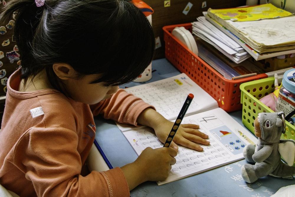 girl in orange long sleeve shirt writing on white paper