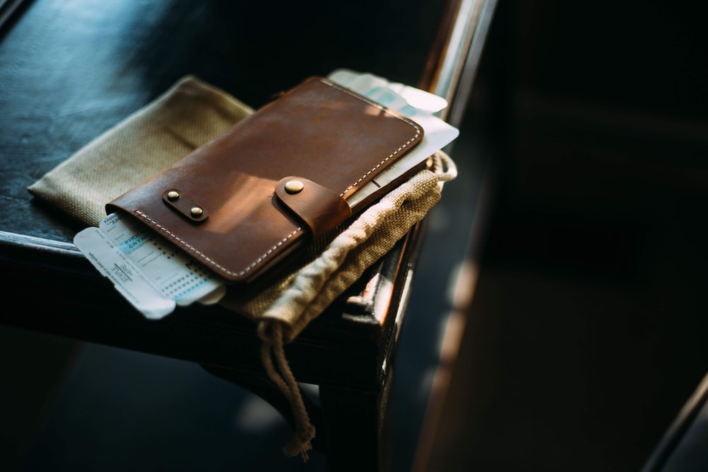 brown leather long wallet on brown wooden chair