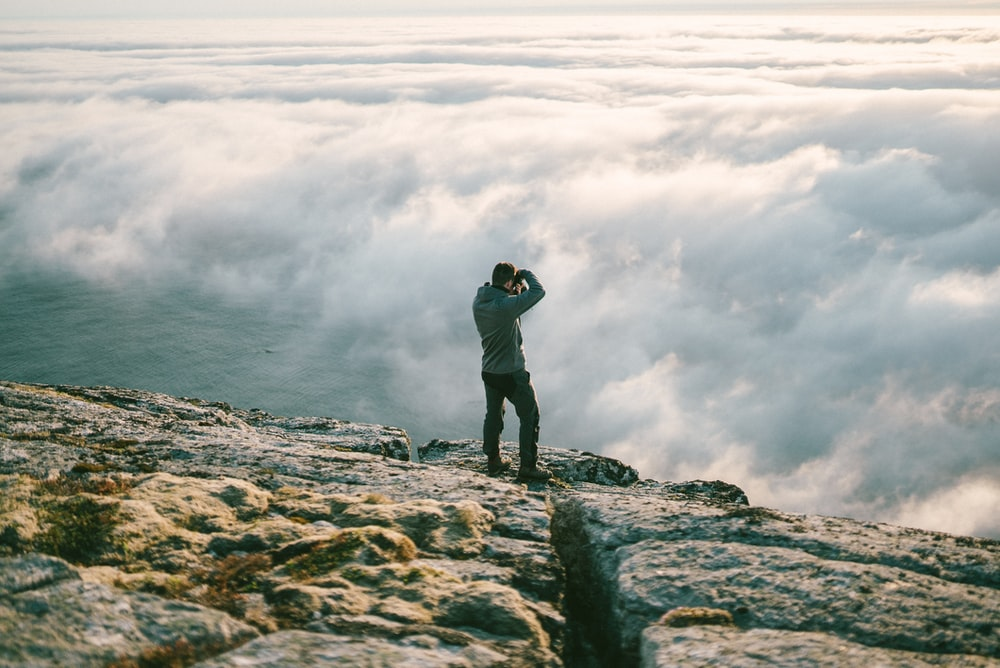 man in black jacket and black pants standing on rock formation near sea of clouds