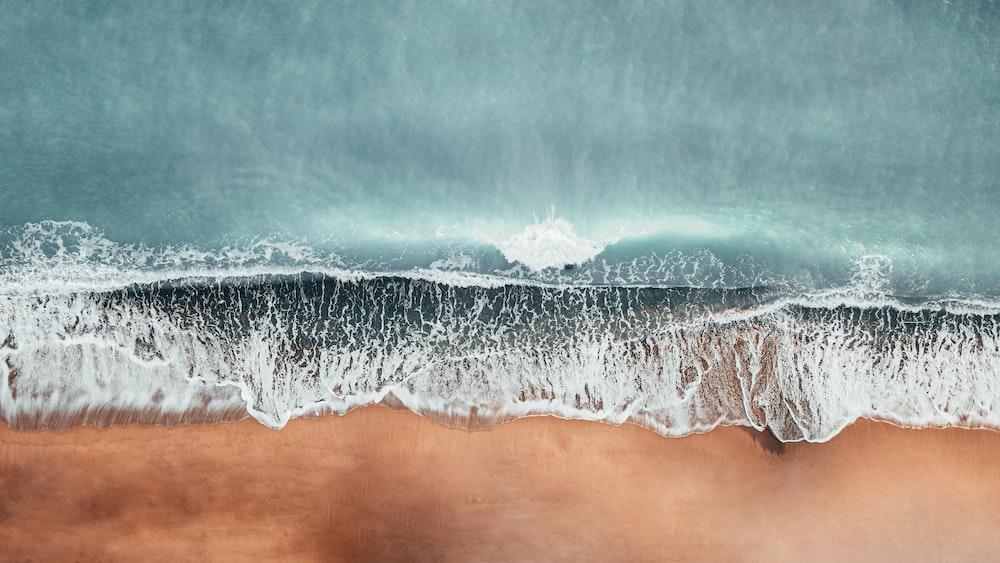 ocean waves on brown sand