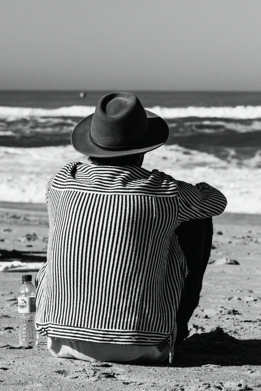 woman in black and white striped long sleeve shirt and black fedora hat standing on beach