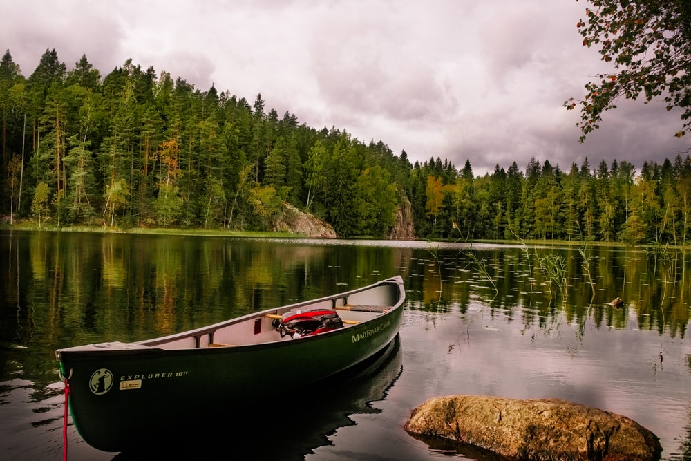 red and white canoe on lake near green trees under white clouds during daytime