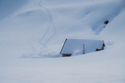 black house on snow covered ground under white clouds