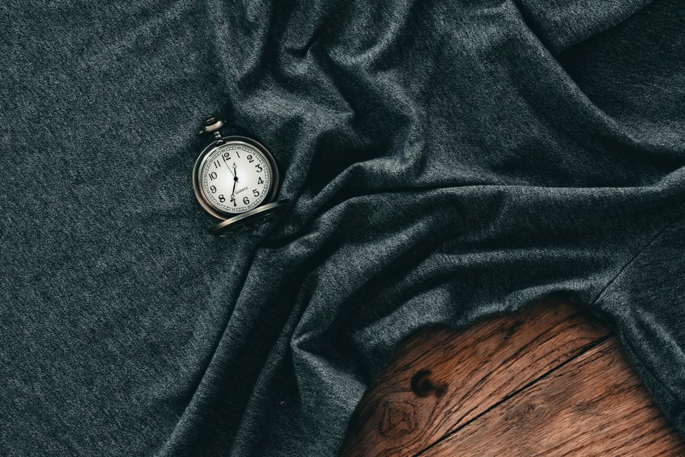 silver and white pocket watch on black textile