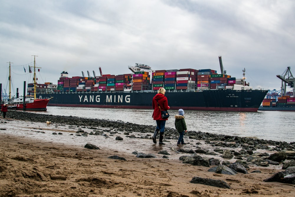 red cargo ship on sea under cloudy sky during daytime