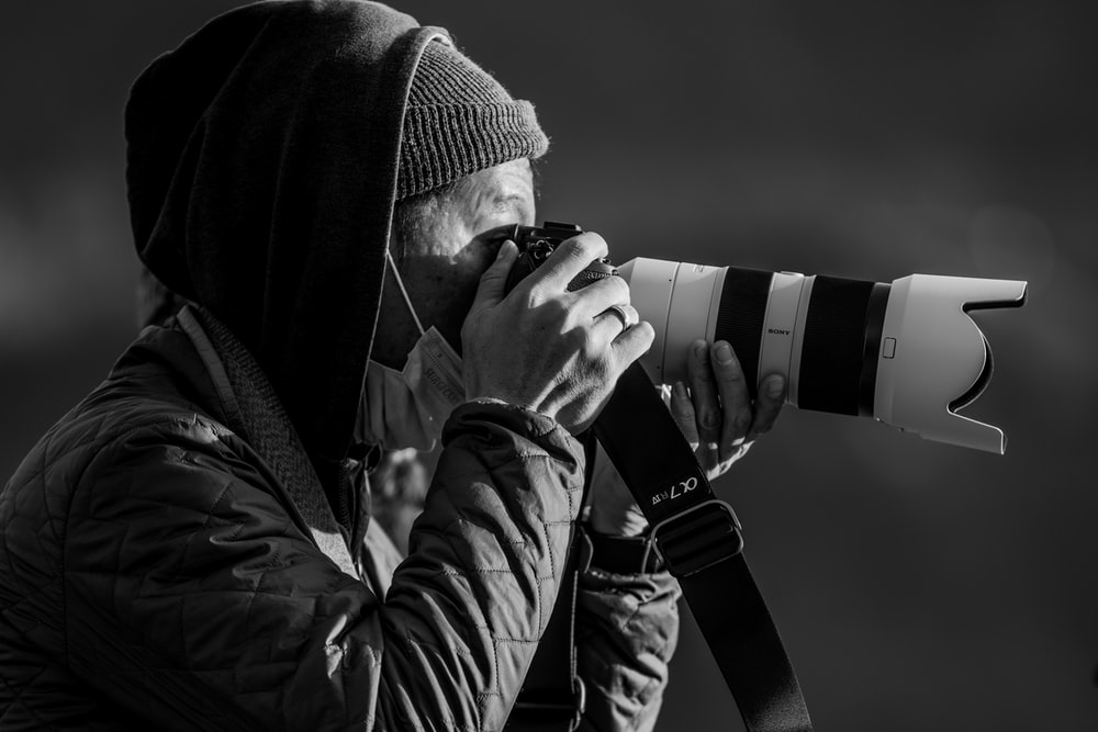 man in black and white jacket holding black and white dslr camera