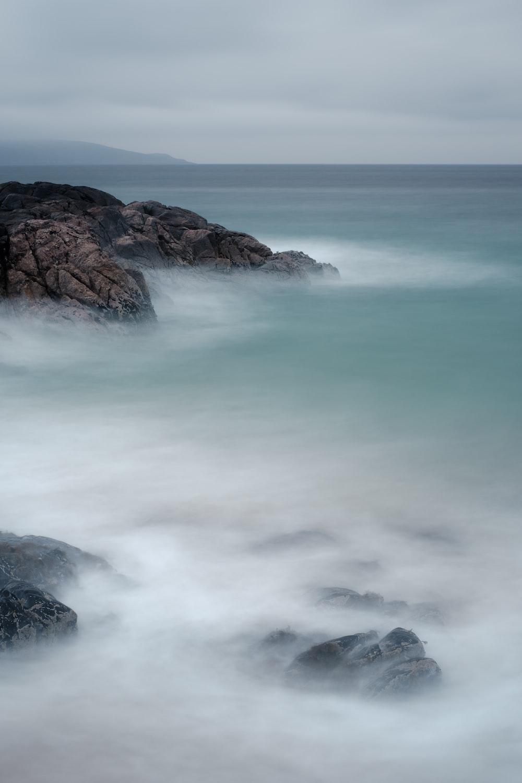 ocean waves crashing on brown rock formation during daytime