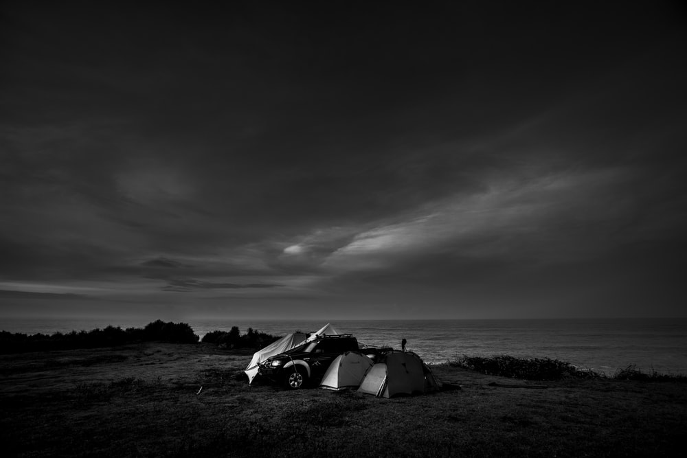 grayscale photo of a car on a field