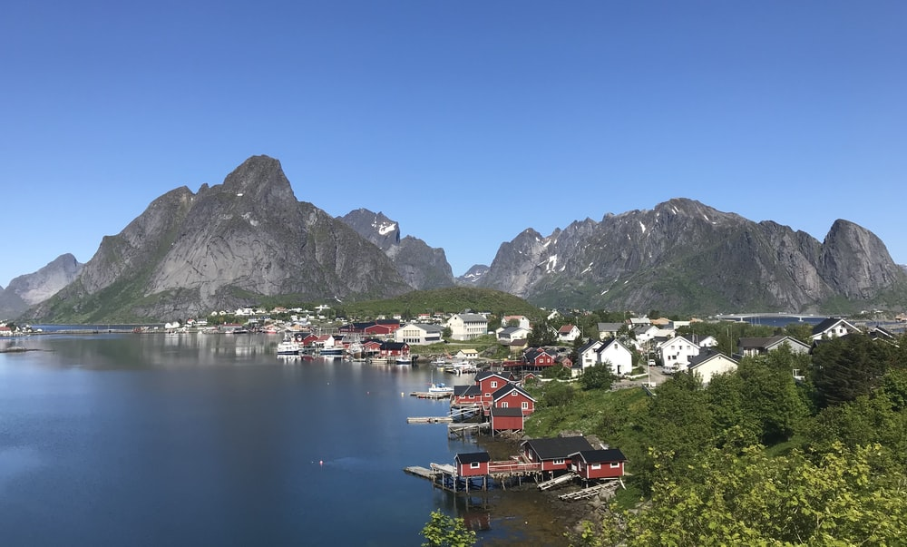 houses near lake and mountains during daytime